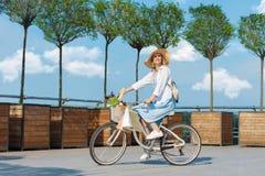 Mujer que completa un ciclo en vestido azul en la bicicleta blanca fotografía de archivo libre de regalías