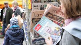 Mujer que compra The Economist Financial Times en el quiosco de la prensa almacen de metraje de vídeo