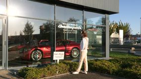 Mujer que compra la nueva ventana del escaparate de la sala de exposición del coche de Maserati almacen de video