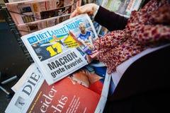 Mujer que compra la prensa internacional con Emmanuel Macron y el infante de marina Fotos de archivo libres de regalías