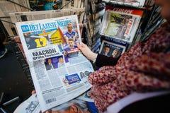 Mujer que compra la prensa internacional con Emmanuel Macron y el infante de marina Imágenes de archivo libres de regalías