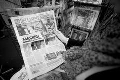 Mujer que compra la prensa internacional con Emmanuel Macron y el infante de marina Imagenes de archivo