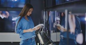 Mujer que compra la TV en una tienda 4k UHD almacen de video