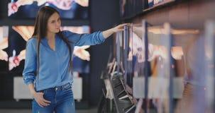 Mujer que compra la TV en una tienda 4k UHD metrajes