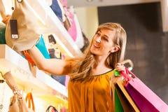 Mujer que compra un bolso en alameda Imagen de archivo