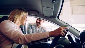 Mujer que compra un coche en la representación que se sienta en su nuevo auto imagenes de archivo