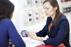 Mujer que compra un smartphone imagenes de archivo
