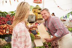 Mujer que compra verduras frescas en la parada del mercado de los granjeros Fotografía de archivo libre de regalías