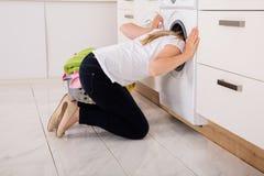 Mujer que comprueba dentro de la lavadora fotos de archivo libres de regalías