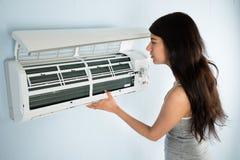 Mujer que comprueba el acondicionador de aire foto de archivo