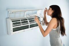 Mujer que comprueba el acondicionador de aire Imagenes de archivo