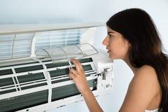 Mujer que comprueba el acondicionador de aire imágenes de archivo libres de regalías