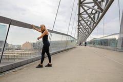 Mujer que comprueba el corazón Rate Using Smartwatch After Workout en el puente imagen de archivo