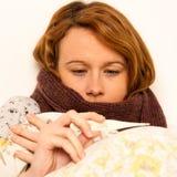 Mujer que comprueba el feaver con la muchacha digital del termomether con gripe fotos de archivo