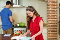 Mujer que comprueba el libro y al hombre de la receta que cocinan en estufa Foto de archivo libre de regalías