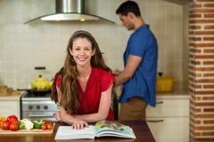 Mujer que comprueba el libro y al hombre de la receta que cocinan en estufa Fotos de archivo libres de regalías