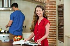 Mujer que comprueba el libro y al hombre de la receta que cocinan en estufa Imágenes de archivo libres de regalías