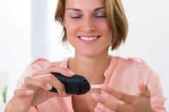 Mujer que comprueba el nivel de la glucosa foto de archivo