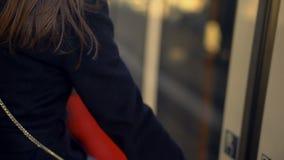 Mujer que comprueba el punto de destino en el teléfono y que entra en el tren, app en línea del boleto almacen de video