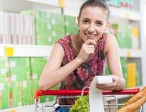 Mujer que comprueba el recibo en el supermercado Fotos de archivo libres de regalías