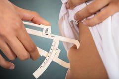 Mujer que comprueba la grasa del estómago con el calibrador imágenes de archivo libres de regalías