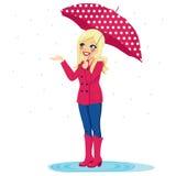 Mujer que comprueba la lluvia Fotos de archivo
