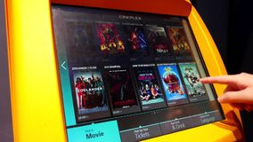 Mujer que comprueba la película que juega tiempo en la máquina del cineplex almacen de metraje de vídeo