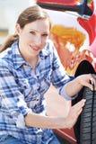 Mujer que comprueba la pisada en el neumático del coche con el indicador foto de archivo