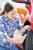 Mujer que comprueba la pisada en el neumático del coche con el indicador imagen de archivo