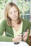 Mujer que comprueba la sangre Sugar Level At Home Fotografía de archivo