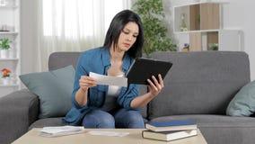 Mujer que comprueba recibos en línea en casa
