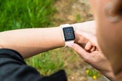 Mujer que comprueba su reloj de Apple Foto de archivo