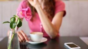 Mujer que comprueba su teléfono que come café almacen de metraje de vídeo