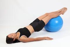 Mujer que concentra en balance usando bola del ejercicio Imagen de archivo