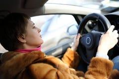 Mujer que conduce el coche Imagenes de archivo