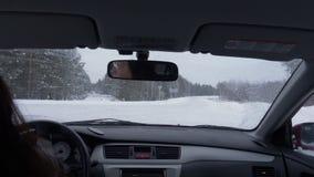 Mujer que conduce el coche en cruce y el camino nevoso en la opinión de día de invierno de asiento trasero metrajes