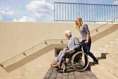 Mujer que conduce el sillón de ruedas abajo Foto de archivo