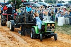 Mujer que conduce el tractor en la tracción de la competencia Imagenes de archivo