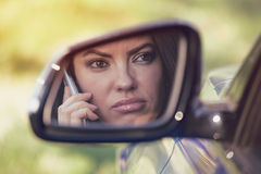 Mujer que conduce en coche y que habla en su teléfono, enfadado por la conversación Fotografía de archivo