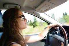 Mujer que conduce un coche Imágenes de archivo libres de regalías