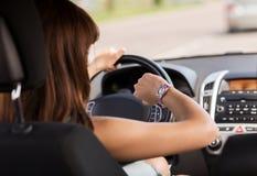 Mujer que conduce un coche y que mira el reloj Imágenes de archivo libres de regalías