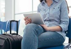 Mujer que conecta en la sala de espera Imagenes de archivo