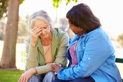 Mujer que conforta al amigo mayor infeliz al aire libre fotografía de archivo libre de regalías