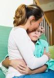Mujer que conforta al hijo gritador del adolescente Foto de archivo libre de regalías