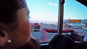 Mujer que considera la ventana exterior del autobús el área de movimiento del aeropuerto metrajes