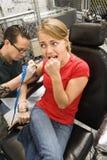 Mujer que consigue el tatuaje. Foto de archivo libre de regalías