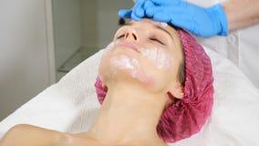 Mujer que consigue el tratamiento cosmético en el salón del balneario Cosmetologist en los guantes médicos que aplican la máscara almacen de metraje de vídeo