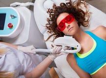 Mujer que consigue el tratamiento de la cara del laser Imágenes de archivo libres de regalías