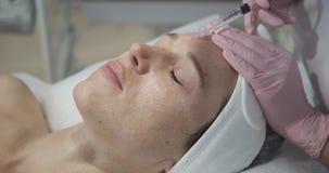Mujer que consigue la inyección cosmética en frente metrajes