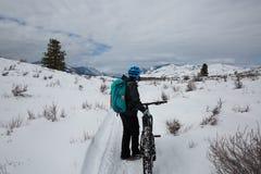 Mujer que consigue lista para montar una bici gorda en las montañas nevosas de la cascada fotografía de archivo